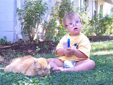 special needs: Young boy playing with cat