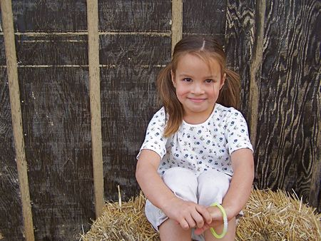 Young girl sitting on bail of hay Stock Photo