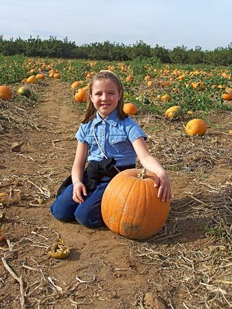 Young girl with pumpkin at the farm