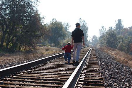 Two boys walking on railroad tracks Foto de archivo