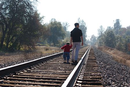 wood railroad: Two boys walking on railroad tracks Stock Photo