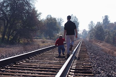 Two boys walking on railroad tracks Stock Photo