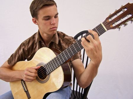 playing folk: Young man with acoustic guitar Stock Photo