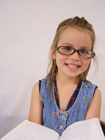 Little girl with glasses and reading