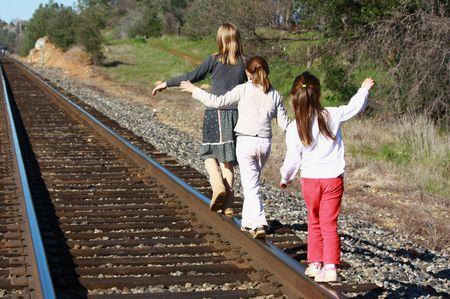 Girls walking on railroad tracks  Foto de archivo