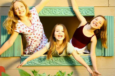 Three girls looking out dollhouse window Stock Photo