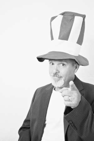 Middle aged man with tall top hat pointing finger at camera. Stock Photo