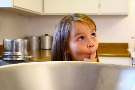 Little girl licking bowl