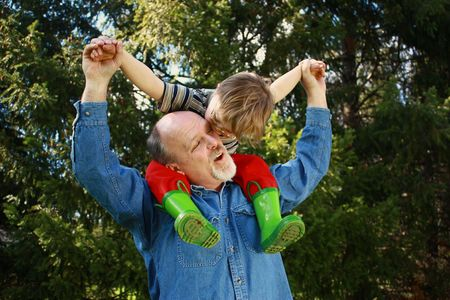 Father with son on shoulders and trees in background