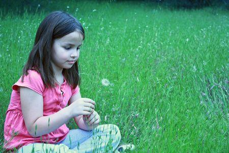 One girl about to blow on dandelion Foto de archivo