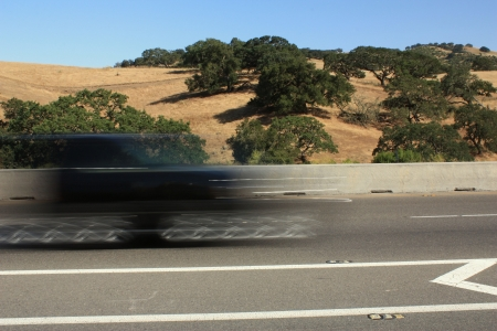 Blurred black vehicle passing by on highway Stock Photo - 7180364