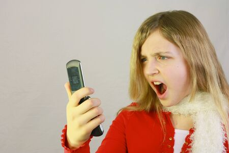 Pretty young girl with shocked expression looking at cell phone Stock Photo - 8764452