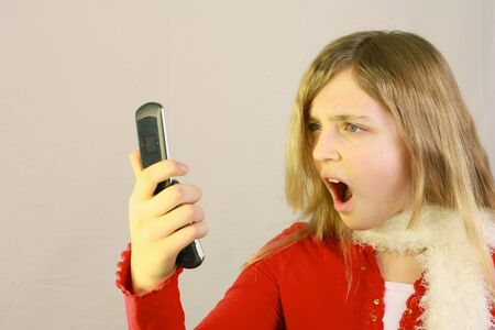 Pretty young girl with shocked expression looking at cell phone Stock Photo - 8764451