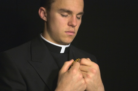rosary: Young Priest praying Stock Photo