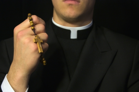 cleric: Young Priest praying the Rosary  Stock Photo