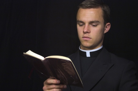 sotana: Sacerdote joven con el libro de la Oración Foto de archivo