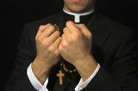 Młody kapłan modli się na różańcu