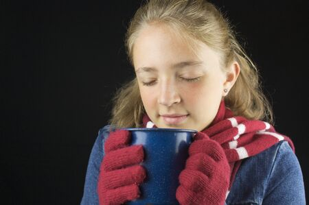 Young blond haired girl wearing winter clothing holding cup Stock Photo - 15713846