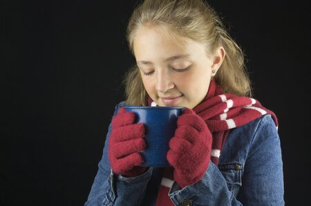 Young blond haired girl wearing winter clothing holding cup Stock Photo - 15713847