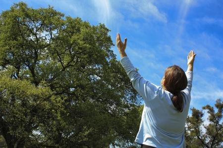alabando a dios: Mujer Alabando a Dios con el cielo azul en el fondo.