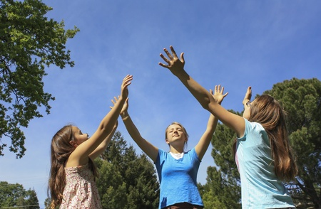 Three girls with hands held up to the sky