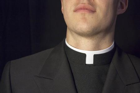sacerdote: Primer plano de cuello Priest con el fondo negro. Foto de archivo