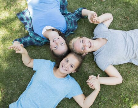 three girls: Three Girls Lying on The Green Grass