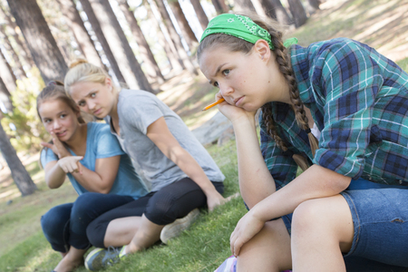 peer pressure: Two Young Girls Gossiping about another Girl