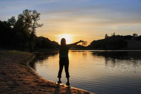 Young Girl Watching the Sun Set With Hands Raised High Stock Photo