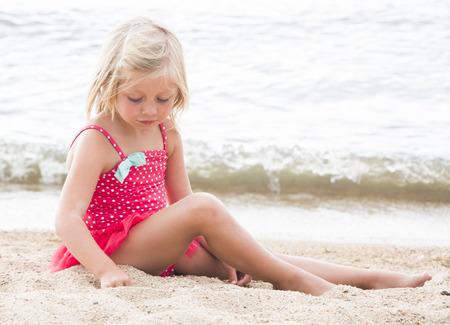 beach blond hair: Cute Little Girl Sunbathing on the Beach