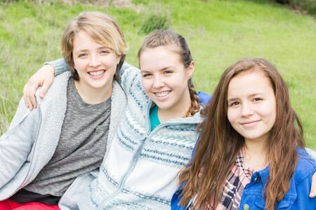 Three Girls Sitting together with green grass in the Background Stock Photo