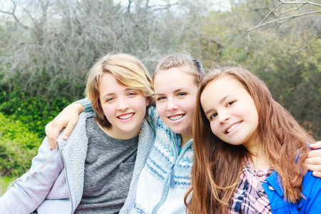 Three Girls Sitting together with green Trees in the Background