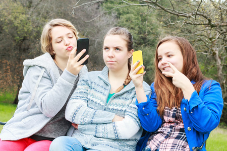 Two Cute Girls Doing Selfies With One Alone