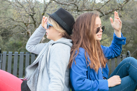 Two Girls Sitting on a Bench with Sunglasses Stock Photo
