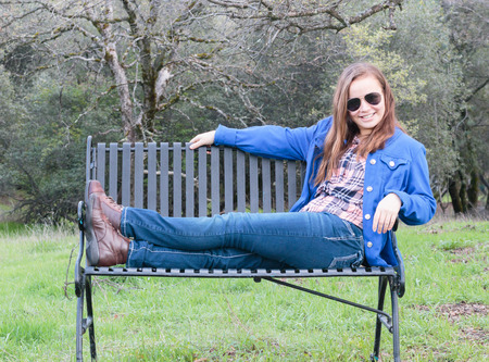 Young Teenage Girl Sitting on Park Bench