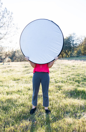 Young Girl Holding up Light Diffuser With Both Hands Stock Photo