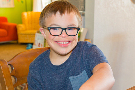 downs syndrome: Young Boy With Downs Syndrome in Blue Shirt Stock Photo