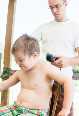 Cute Little Boy With Downs Syndrome Geting His Haircut