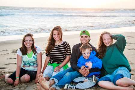 Brothers and Sisters Sitting Together on Sandy Beach photo