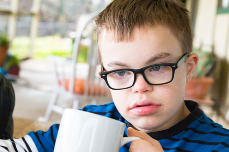 Close up of Young Boy With Downs Syndrome Holding Cup photo