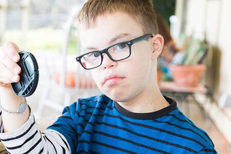 Close up of Young Boy With Downs Syndrome Holding Lens Cap photo
