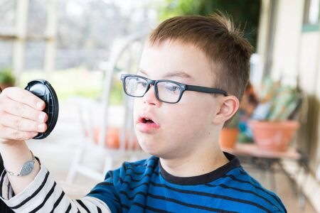 Close up of Young Boy With Downs Syndrome Lens Cap photo