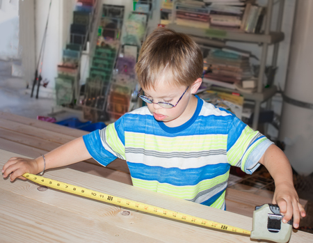 Young Boy With Downs Syndrome Playing With Measuring Tape photo
