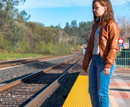Cute Young Girl Standing Near Train Rails Imagens