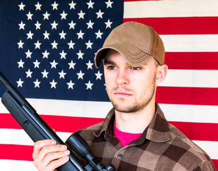 Young Man With Shotgun on American Flag Background Stock Photo