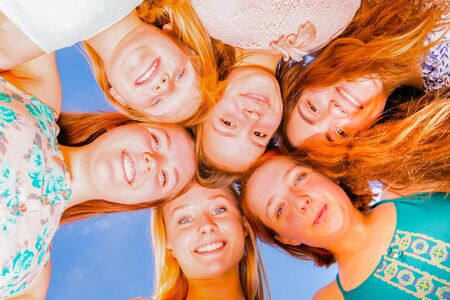 bakground: Young Girls With Heads Together Looking Down With Blue Sky in the Bakground