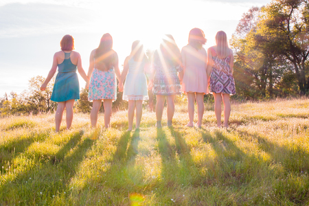 Young Girls Standing Together in Grassy Field Facing the Bright Sunset Stock Photo