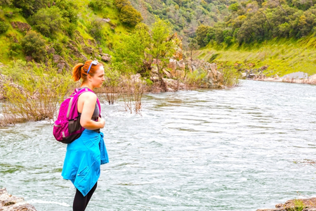 Young Girl Standing on Rocks Near Fast River 免版税图像