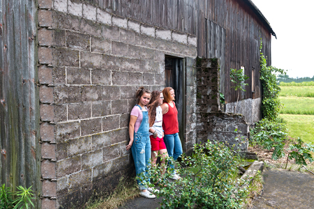 leaning against: Three Girls Leaning Against Brickwall of Old Gray Barn Stock Photo