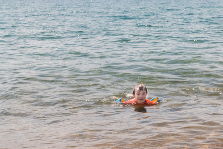 Little Boy With Downs Syndrome Playing in the Water at the Beach